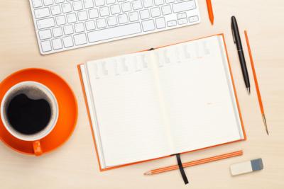 gauche une tasse avec du café et autour un crayon de papier, une gomme et un stylo